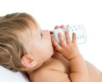 Baby holding bottle and drinking Royalty Free Stock Image