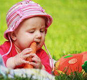 Baby holding a carrot in his hand Stock Photos