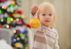 Baby holding Christmas ball near Christmas tree Royalty Free Stock Photo