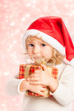 Baby holding Christmas gift in hands Stock Photo