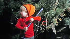 1973: Baby holding a Christmas tree saw to mimic Dad. stock footage