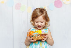 Baby holding Easter eggs. Happy little girl holding Easter eggs royalty free stock image