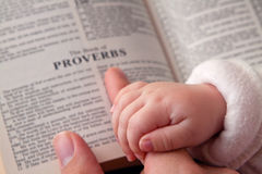 Baby Holding Dad's Finger on Bible. Baby holding father's finger as he points to Proverbs verse Stock Photo