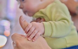 Baby holding father´s finger stock photo
