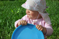 Baby holding frisbee. Baby girl sitting on the grass and holding blue frisbee Stock Photo