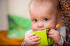 Baby holding a green block facing Royalty Free Stock Photography