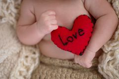 Baby Holding a Heart Shaped Pillow Royalty Free Stock Photography
