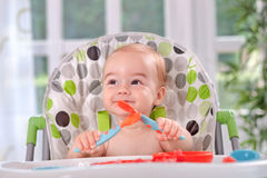 Baby holding itself with a spoon and fork Stock Photos