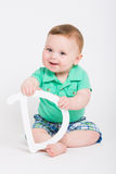 Baby Holding Letter D Smirk. 8 month year old baby sits on a white background holding a white letter D looking at camera smiling. dressed in a cute green polo stock image
