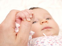 Baby holding parents hand Stock Photo
