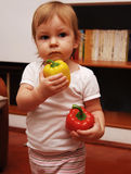 Baby holding peppers. An adorable baby holding a yellow and a red bell pepper in her hands Stock Photo