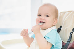 Baby holding a spoon in his mouth and laughs Royalty Free Stock Images