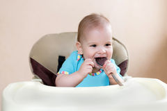 Baby holding a spoon in his mouth and laughs Royalty Free Stock Image