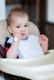 Baby holding a spoon in his mouth and laughs Royalty Free Stock Photo