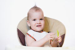 Baby holding a spoon in his mouth Stock Photography