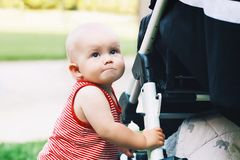 Baby holding on to the stroller Stock Image