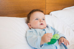 Baby holding toy in bed Royalty Free Stock Photos
