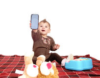 Baby holding up a cell phone. Royalty Free Stock Photos