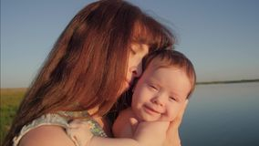 Baby is holding young mother in her arms and smiling. Slow motion. stock footage