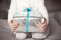 Baby holds a Christmas present box in hands Stock Image