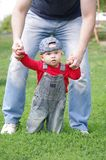 Baby holds on fathers hands outdoors Stock Photo