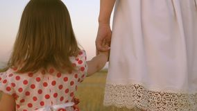 Baby holds mom`s hand, a happy family walks in the evening out of town. Mom walks on the field with her little daughter stock footage
