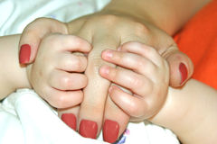 Baby Holds Mother's Hand. Infant holds onto mother's fingers while napping Stock Image