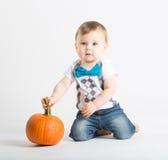 Baby Holds Pumpkin Stem Kneeling Royalty Free Stock Image