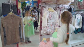 Baby holds rack with dresses in emporium. Little girl trying on clothes in the shop. Happy customer standing in front of mirror holding two beautiful dress in stock footage