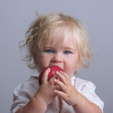Baby holds a red apple eating. Baby with blond long hair holds a red apple eating royalty free stock photography