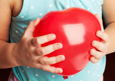 Baby holds red heart shaped balloon Royalty Free Stock Images