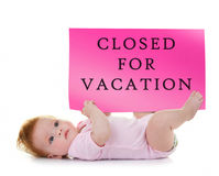 Baby holds a signboard that says closed for vacation Stock Photo