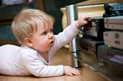 Baby with home video. Baby girl crawling on the floor, messing with home audio video equipment stock images