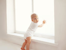 Baby at home in white room stands near window Royalty Free Stock Photo