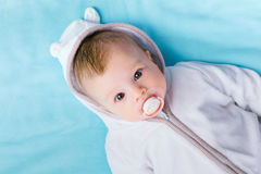 Baby in the hood on a blue blanket Stock Image