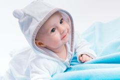Baby in the hood on a blue blanket Royalty Free Stock Photos