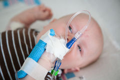 Baby in Hospital With an IV in their Hand. Baby in hospital bed getting IV medicine treatment stock photography