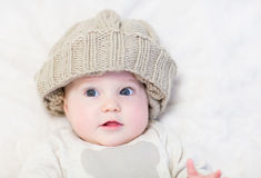 Baby in a huge knitted hat Stock Photo