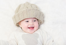 Baby in a huge knitted hat Stock Images