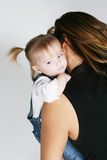 Baby hugged by mother. Cute baby being hugged and carried by mother Stock Photo