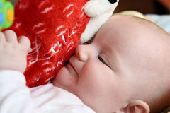 Baby hugging big plush heart Stock Photo