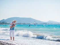 Baby hugging mother standing at sea shore Royalty Free Stock Photos