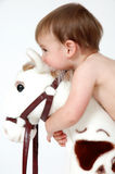 Baby Hugs. Little baby boy hugging the head of a horse toy. Baby boy resting his chin on a horses head looking in front of him Royalty Free Stock Photography