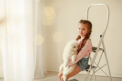 Baby Hugs the white fluffy puppy. Kids stock photo