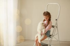 Baby Hugs the white fluffy puppy. Kids stock photos