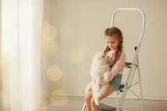 Baby Hugs the white fluffy puppy. Kids.  royalty free stock photo