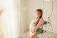 Baby Hugs the white fluffy puppy. Kids royalty free stock photo