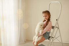Baby Hugs the white fluffy puppy. Kids royalty free stock photography