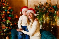 Baby Hugs a young woman in the Christmas room royalty free stock image