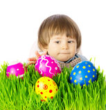 Baby hunting for easter eggs. Cute Baby boy hunting for colorful Easter Eggs, hidden in the green grass, close up face portrait. Studio shot, over white Stock Photo